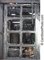 Charred window of a burnt house