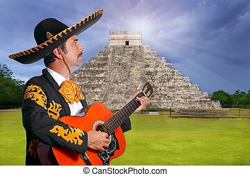Charro Mariachi playing guitar in Chichen Itza pyramid...
