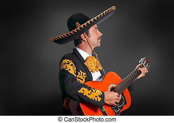 Charro Mariachi playing guitar on black