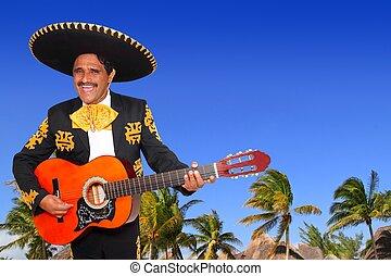 Charro mexican Mariachi playing guitar in beach