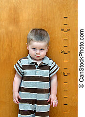 Charting his Growth - Little boy stands against a wooden...