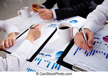 Charts and graphs - Hands of business people during...