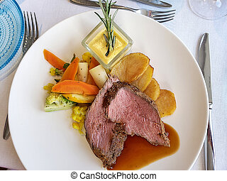 Chateaubriand with colorful vegetables and sliced potatoes on white plate with Bearnaise sauce