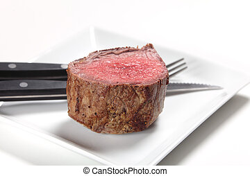 A chateaubriand or tenderloin steak on a plate with a steak knife and fork