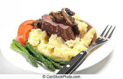 Chateaubriand beef tenderloin steak topped with a mushroom gravy sauce served on a bed of potato with asparagus and slices of tomato.