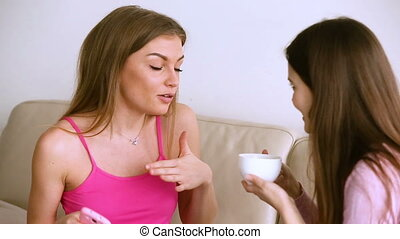Chatter talk of two young women, girls gossiping drinking coffee