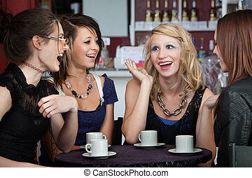 Chatting in a Coffee Shop - Four college freshmen chatting...