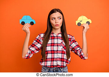 Cheap or expensive concept. Close up photo of unsatisfied unhappy pondering planning pensive woman choosing way of traveling holding two different cars in hands isolated background