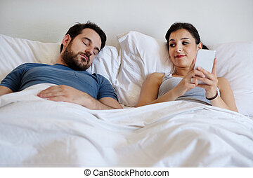 Cheating wife using mobile phone lying in bed next to his sleeping husband