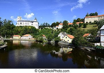 Rozmberk nad Vltavou, Czechia - Ausgust 11th 2013: Castle Rozmberk and homes reflecting in river Mltava (Moldau)
