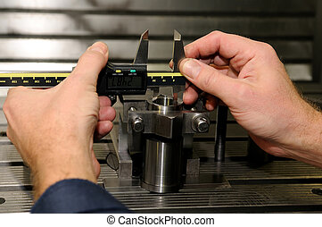 Check measurement of a bore in a metal blank in attachment by hand caliper