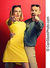 Check this out. Happy young couple isolated on red background