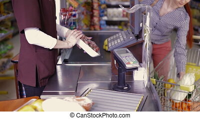 Check till and products on conveyor belt - Woman at cash box...