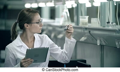 Check-up List - Woman of science working in laboratory...