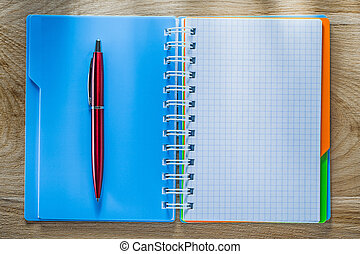 Checked copybook pen on wooden board