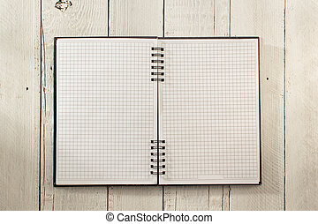 checked notebook on wood