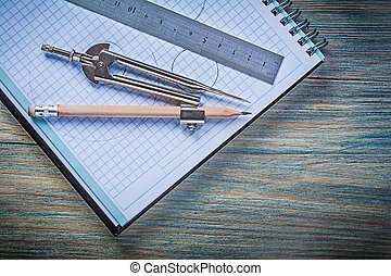 Checked notepad metal ruler drawing compass pencil on vintage wo