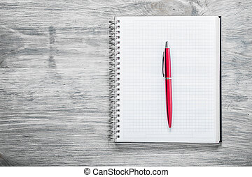 Checked notepad pen on wooden board education concept