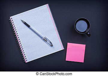 Checked notepad pen sticky note and cup of coffee on black backg