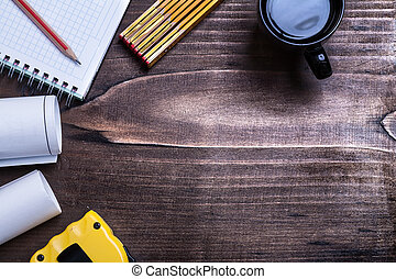 Checked notepad pencil blueprints tape line wooden meter and cup