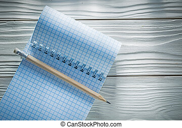 Checked spiral blank notepad pencil on white wooden board