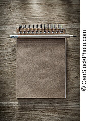 Checked spiral notebook on wooden board directly above