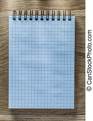 Checked spiral notebook pencil on wooden board directly above