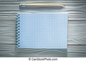 Checked spiral notepad pencil on white wooden board
