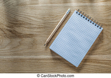 Checked spiral notepad pencil on wooden board directly above