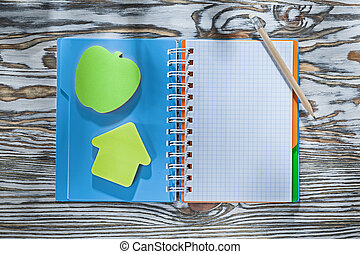 Checked spiral notepad pencil sticky reminders on wooden board