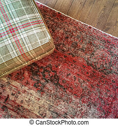 Checked textile hassock and vintage style carpet. Interior design.