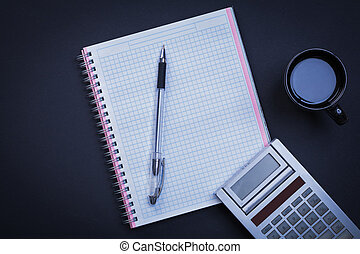 Checked workbook pen calculator and cup of coffee on black backg