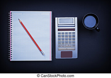 Checked workbook pencil calculator and cup of coffee on black ba
