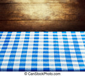 Checkered blue tablecloth over rustic wooden background