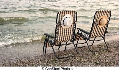 Checkered deck chairs on the sandy beach. Romantic summer...