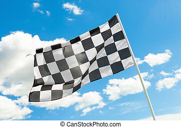 Checkered flag waving in the wind with white clouds on...
