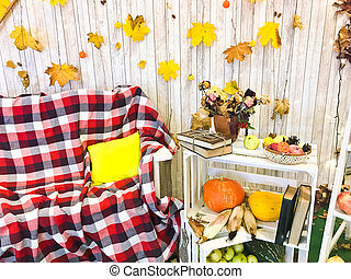 Checkered plaid on an armchair and a wooden table with vintage books tied with twine and a vase, herbarium, green apple on the background of wooden boards and yellow autumn leaves.