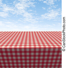 Checkered tablecloth table with a blank empty picnic cloth in perspective on a blue sunny summer sky as a symbol of food and leisure fun.