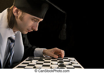 Checkers - Student in a cloak plays checkers on a white...