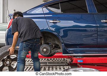 Checking a car suspension for repair at car garage -...