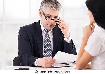 Checking a report. Thoughtful grey hair man in formalwear looking at the paper and adjusting glasses while woman sitting in front of him and holding hand on chin