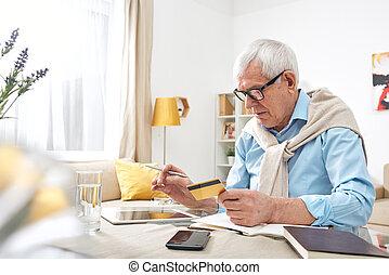 Checking balance of debit card - Busy elderly wrinkled man ...