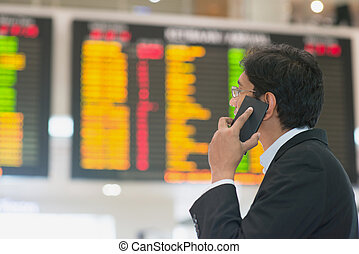 Checking flight timetable - Asian Businessman looking at...