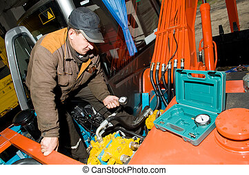 serviceman repairman checking hydraulic pressure by measuring it with manometer