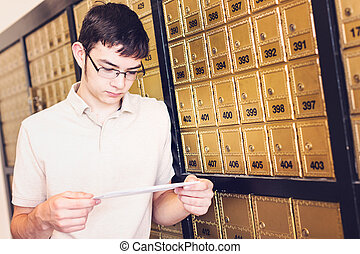 Checking mail - College student checking mail at mailboxed.