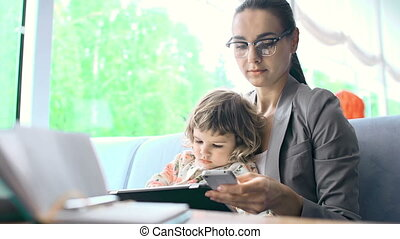 Checking Mobile Mail - Close up of woman with a child in her...