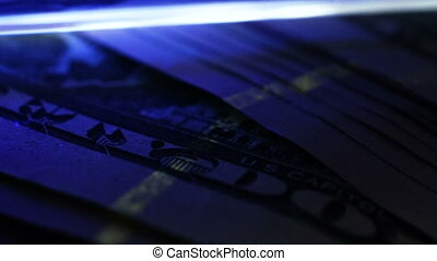 Checking of dollar banknotes under UV detector. Counterfeit...