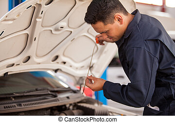 Handsome Latin mechanic measuring the oil level of an engine at an auto shop