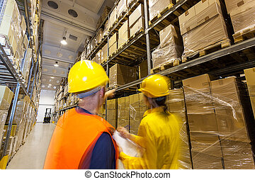 Two managers checking products in huge warehouse