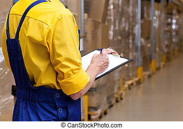 Checking stock condition - Closeup of a worker with list ...